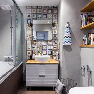 Новый формат декора квартиры: маленькая главная ванная комната в современном стиле с инсталляцией, серыми стенами, столешницей из дерева, серыми фасадами, ванной в нише, душем над ванной, разноцветной плиткой, цементной плиткой, настольной раковиной, коричневым полом, душем с раздвижными дверями, плоскими фасадами и коричневой столешницей