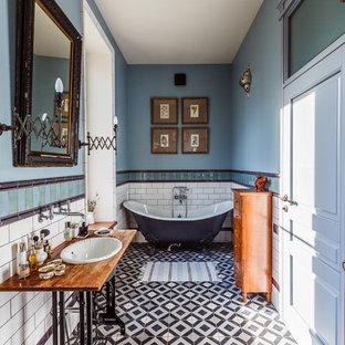 Foto di una grande stanza da bagno padronale eclettica con vasca con piedi a zampa di leone, vasca/doccia, piastrelle multicolore, piastrelle di cemento, pavimento con piastrelle in ceramica, lavabo sottopiano, top in legno, pareti blu, pavimento multicolore e top marrone