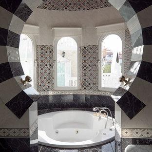 Ejemplo de cuarto de baño principal, mediterráneo, de tamaño medio, con jacuzzi, baldosas y/o azulejos blancas y negros, baldosas y/o azulejos de cerámica, suelo de baldosas de cerámica, encimera de mármol y paredes multicolor
