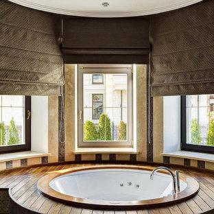 Стильный дизайн: главная ванная комната в современном стиле с полновстраиваемой ванной, бежевой плиткой и коричневым полом - последний тренд