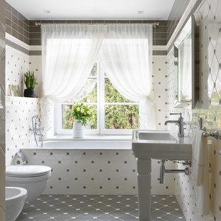На фото: главная ванная комната в стиле современная классика с ванной в нише, инсталляцией, белой плиткой, серой плиткой, консольной раковиной и серым полом с