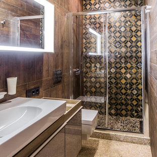 Создайте стильный интерьер: ванная комната в современном стиле с плоскими фасадами, душем в нише, коричневой плиткой, черной плиткой, полом из мозаичной плитки, душевой кабиной, бежевым полом, душем с раздвижными дверями, коричневыми фасадами, инсталляцией, коричневыми стенами и настольной раковиной - последний тренд