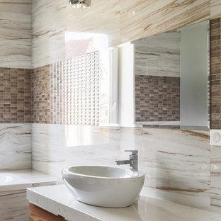 Создайте стильный интерьер: главная ванная комната среднего размера в современном стиле с плоскими фасадами, фасадами цвета дерева среднего тона, накладной ванной, керамогранитной плиткой, полом из керамогранита, настольной раковиной, столешницей из искусственного кварца и бежевым полом - последний тренд