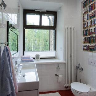 На фото: ванная комната в современном стиле с плоскими фасадами, белыми фасадами, инсталляцией, белой плиткой, белыми стенами, душевой кабиной, консольной раковиной и красным полом с