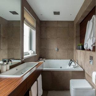 На фото: главная ванная комната в современном стиле с плоскими фасадами, фасадами цвета дерева среднего тона, коричневой плиткой, гидромассажной ванной, накладной раковиной, столешницей из дерева и коричневой столешницей с