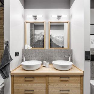 На фото: ванная комната среднего размера в стиле неоклассика (современная классика) с плоскими фасадами, светлыми деревянными фасадами, серой плиткой, белыми стенами, полом из керамогранита, душевой кабиной, настольной раковиной, столешницей из дерева, серым полом, бежевой столешницей, тумбой под две раковины и встроенной тумбой