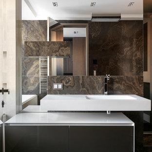 Стильный дизайн: большая главная ванная комната в современном стиле с плоскими фасадами, серыми фасадами, коричневой плиткой, мраморной плиткой, мраморным полом, монолитной раковиной, белой столешницей и серым полом - последний тренд