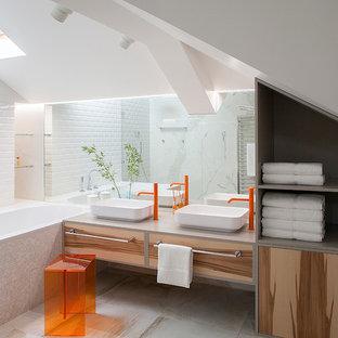 На фото: главная ванная комната в современном стиле с плоскими фасадами, накладной ванной, белой плиткой, плиткой кабанчик, белыми стенами, настольной раковиной, бежевым полом, серой столешницей и светлыми деревянными фасадами с
