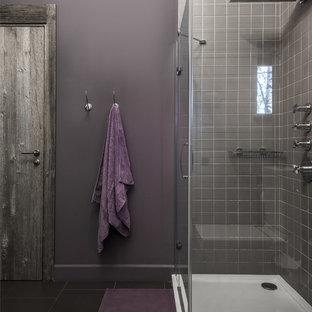 Пример оригинального дизайна интерьера: ванная комната в современном стиле с серой плиткой, фиолетовыми стенами, душевой кабиной, черным полом и душем с распашными дверями
