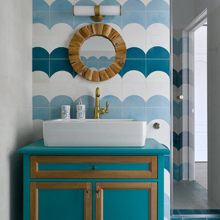 Modelo de cuarto de baño actual con armarios con paneles empotrados, puertas de armario turquesas, baldosas y/o azulejos azules, baldosas y/o azulejos blancos, lavabo sobreencimera, suelo azul y encimeras turquesas
