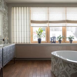 Свежая идея для дизайна: большая главная ванная комната в современном стиле с серыми фасадами, серыми стенами, темным паркетным полом, коричневым полом, плоскими фасадами, отдельно стоящей ванной, белой столешницей, столешницей из искусственного камня, монолитной раковиной, душем над ванной и открытым душем - отличное фото интерьера