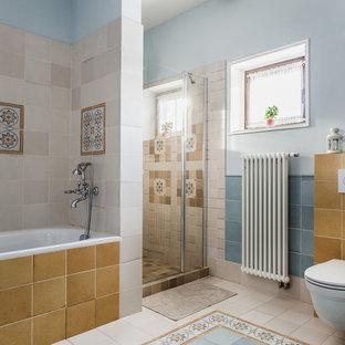 Ejemplo de cuarto de baño principal, clásico, de tamaño medio, con bañera empotrada, ducha empotrada, sanitario de pared, baldosas y/o azulejos azules, baldosas y/o azulejos beige, baldosas y/o azulejos multicolor, paredes azules, suelo de baldosas de cerámica, suelo multicolor, ducha con puerta con bisagras y baldosas y/o azulejos de cerámica