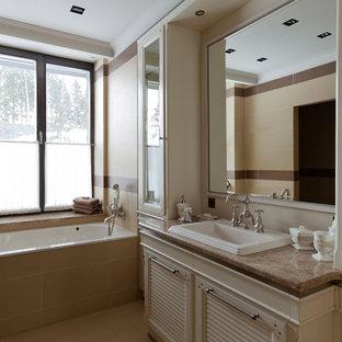 На фото: главная ванная комната в классическом стиле с фасадами с филенкой типа жалюзи, бежевыми фасадами, ванной в нише, бежевой плиткой, накладной раковиной, бежевым полом и бежевой столешницей с