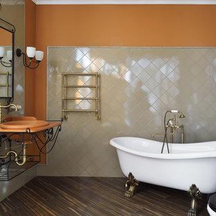 Foto di una stanza da bagno padronale classica con vasca con piedi a zampa di leone, WC a due pezzi, piastrelle beige, pareti arancioni, lavabo da incasso, pavimento marrone e top arancione
