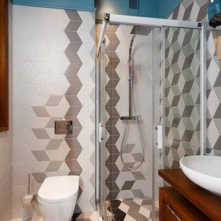 Modelo de cuarto de baño con ducha, escandinavo, pequeño, con armarios con paneles empotrados, puertas de armario de madera oscura, ducha esquinera, sanitario de pared, baldosas y/o azulejos blancos, baldosas y/o azulejos grises, baldosas y/o azulejos negros, paredes azules, lavabo sobreencimera, suelo multicolor y ducha con puerta corredera