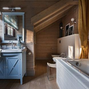 На фото: главная ванная комната в стиле рустика с фасадами с утопленной филенкой, синими фасадами, накладной ванной, серой плиткой, плиткой кабанчик, тумбой под одну раковину, напольной тумбой, деревянными стенами, деревянным потолком и светлым паркетным полом с