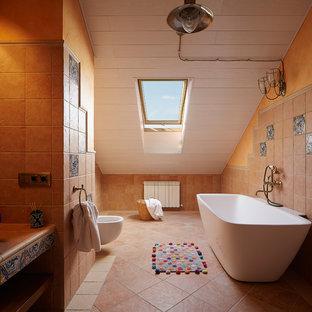 Immagine di una piccola stanza da bagno per bambini mediterranea con vasca freestanding, WC sospeso, piastrelle beige, piastrelle in pietra, pareti beige, pavimento in terracotta e top alla veneziana