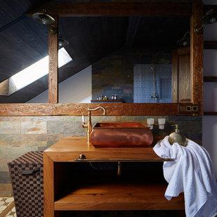 Imagen de cuarto de baño con ducha, rural, de tamaño medio, con puertas de armario de madera en tonos medios, ducha esquinera, baldosas y/o azulejos beige, baldosas y/o azulejos de piedra, paredes marrones, suelo de baldosas de terracota, lavabo sobreencimera, encimera de madera, armarios abiertos y encimeras marrones
