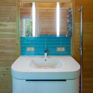 Foto de cuarto de baño actual, de tamaño medio, con armarios con paneles lisos, baldosas y/o azulejos azules, baldosas y/o azulejos de cerámica, paredes marrones, suelo de baldosas de porcelana, puertas de armario blancas y lavabo integrado