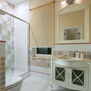Пример оригинального дизайна: ванная комната среднего размера в стиле неоклассика (современная классика) с душем в нише, инсталляцией, разноцветной плиткой, бежевыми стенами, душевой кабиной, врезной раковиной, белым полом, душем с раздвижными дверями и бежевой столешницей