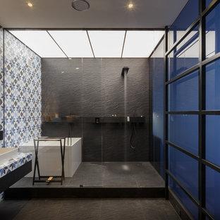 На фото: главные ванные комнаты в современном стиле с угловой ванной, душевой комнатой, разноцветной плиткой, настольной раковиной и черным полом
