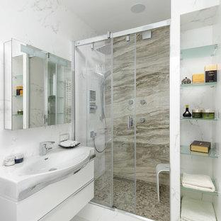 Удачное сочетание для дизайна помещения: ванная комната в современном стиле с плоскими фасадами, белыми фасадами, душем в нише, душевой кабиной, белым полом, разноцветной плиткой, плиткой из листового камня, белыми стенами, душем с раздвижными дверями, унитазом-моноблоком, полом из керамогранита и настольной раковиной - самое интересное для вас