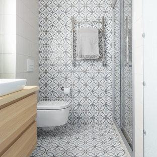 Пример оригинального дизайна интерьера: маленькая ванная комната в современном стиле с плоскими фасадами, фасадами цвета светлого дерева, душем в нише, инсталляцией, керамогранитной плиткой, полом из керамогранита, душевой кабиной, столешницей из дерева, разноцветным полом, душем с раздвижными дверями, настольной раковиной и бежевой столешницей