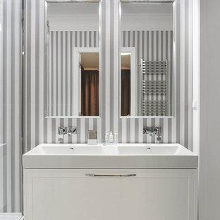На фото: большая ванная комната в современном стиле с фасадами с утопленной филенкой, белыми фасадами, душевой кабиной, раковиной с несколькими смесителями и серым полом с