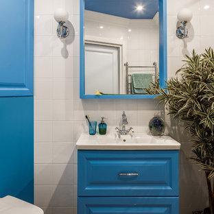 На фото: ванная комната в современном стиле с фасадами с выступающей филенкой, синими фасадами, инсталляцией, белой плиткой, монолитной раковиной и разноцветным полом с