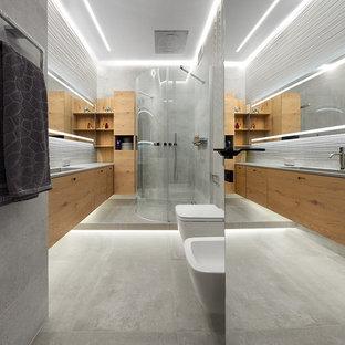 Создайте стильный интерьер: большая ванная комната в современном стиле с плоскими фасадами, фасадами цвета дерева среднего тона, душем без бортиков, раздельным унитазом, серой плиткой, душевой кабиной, монолитной раковиной, серым полом, душем с распашными дверями и белой столешницей - последний тренд