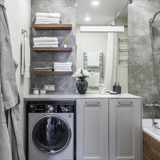 Пример оригинального дизайна: маленькая ванная комната в стиле современная классика с полновстраиваемой ванной, душем над ванной, инсталляцией, серой плиткой, белыми стенами, полом из керамогранита, врезной раковиной, серым полом и шторкой для ванной