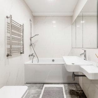 На фото: со средним бюджетом главные ванные комнаты среднего размера в современном стиле с душем над ванной, инсталляцией, полом из керамической плитки, серым полом, подвесной раковиной, ванной в нише и белой плиткой