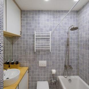На фото: маленькая главная ванная комната в современном стиле с душем над ванной, синей плиткой, керамической плиткой, полом из керамогранита, столешницей из дерева, плоскими фасадами, белыми фасадами, ванной в нише, настольной раковиной, унитазом-моноблоком, разноцветными стенами и шторкой для душа с