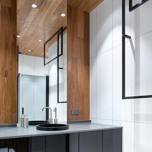 На фото: ванная комната среднего размера в современном стиле с плоскими фасадами, черными фасадами, душем в нише, белой плиткой, керамогранитной плиткой, душевой кабиной, накладной раковиной, столешницей из гранита, душем с распашными дверями и серой столешницей с