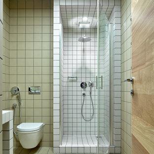 Modelo de cuarto de baño con ducha, nórdico, pequeño, con sanitario de pared, suelo de azulejos de cemento, encimera de azulejos, ducha empotrada, baldosas y/o azulejos beige, paredes beige, suelo multicolor y ducha con puerta con bisagras