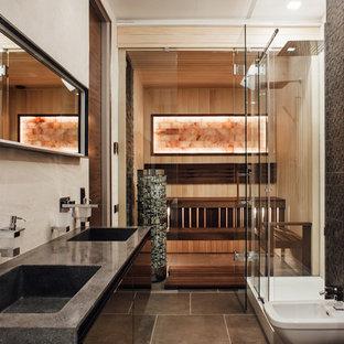 Неиссякаемый источник вдохновения для домашнего уюта: главная ванная комната в современном стиле с плоскими фасадами, черными фасадами, душем в нише, бежевой плиткой, черной плиткой, монолитной раковиной, серым полом, душем с распашными дверями и черной столешницей