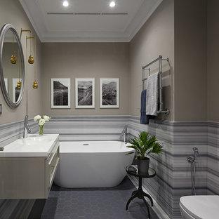 Выдающиеся фото от архитекторов и дизайнеров интерьера: главная ванная комната в современном стиле с отдельно стоящей ванной, серой плиткой, разноцветной плиткой, белой плиткой, бежевыми стенами, монолитной раковиной, серым полом, белой столешницей, плоскими фасадами и серыми фасадами