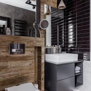 Пример оригинального дизайна: ванная комната среднего размера в стиле лофт с инсталляцией, черной плиткой, керамической плиткой, серыми стенами, полом из керамогранита, душевой кабиной, столешницей из искусственного камня, коричневым полом, серой столешницей, плоскими фасадами, серыми фасадами и настольной раковиной