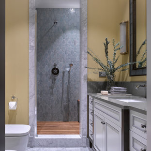 Пример оригинального дизайна: ванная комната среднего размера в стиле современная классика с белыми фасадами, душем в нише, биде, керамической плиткой, желтыми стенами, мраморным полом, душевой кабиной, столешницей из искусственного кварца, душем с распашными дверями, фасадами с утопленной филенкой, серой плиткой, врезной раковиной и серым полом