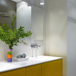 Foto di una stanza da bagno per bambini contemporanea di medie dimensioni con ante lisce, ante gialle, piastrelle bianche, pareti beige, lavabo rettangolare e top bianco