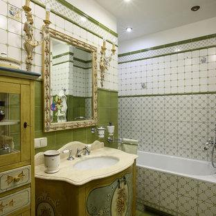 На фото: ванная комната в викторианском стиле с ванной в нише, белой плиткой, зеленой плиткой и врезной раковиной