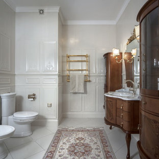 Example of an ornate white tile bathroom design in Saint Petersburg with marble countertops, a two-piece toilet, an undermount sink, furniture-like cabinets, dark wood cabinets and beige walls