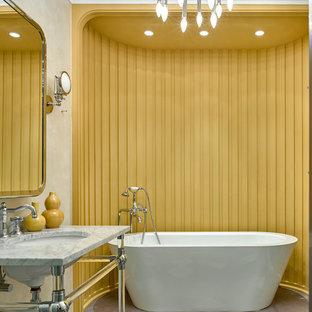 Inredning av ett klassiskt grå grått en-suite badrum, med ett fristående badkar, flerfärgad kakel, gula väggar, ett konsol handfat, marmorbänkskiva, flerfärgat golv och öppna hyllor