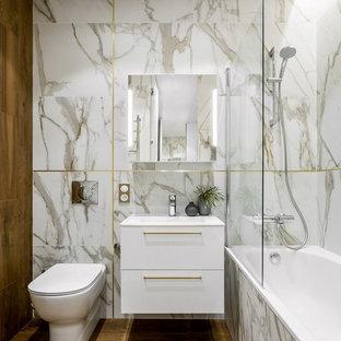 На фото: с невысоким бюджетом маленькие главные ванные комнаты в современном стиле с плоскими фасадами, белыми фасадами, полом из керамогранита, коричневым полом, ванной в нише, душем над ванной, раздельным унитазом, белой плиткой, монолитной раковиной и открытым душем