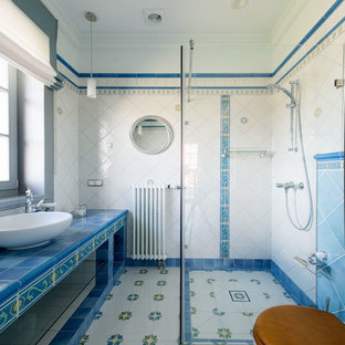 Großes Mediterranes Duschbad mit weißen Schränken, offener Dusche, farbigen Fliesen, Keramikfliesen, weißer Wandfarbe, Porzellan-Bodenfliesen, buntem Boden, Schiebetür-Duschabtrennung, Aufsatzwaschbecken, gefliestem Waschtisch und blauer Waschtischplatte