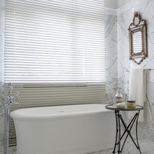 На фото: ванная комната в классическом стиле с отдельно стоящей ванной, белой плиткой, серой плиткой, плиткой из листового камня и белыми стенами с