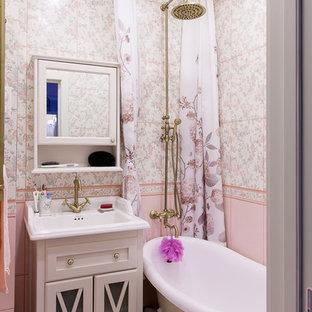 Idee per una piccola stanza da bagno padronale tradizionale con vasca con piedi a zampa di leone, piastrelle rosa, ante di vetro, ante bianche, vasca/doccia, pareti rosa, lavabo a consolle e doccia con tenda