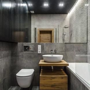 Foto på ett mellanstort industriellt brun badrum med dusch, med släta luckor, skåp i mellenmörkt trä, en dusch/badkar-kombination, en vägghängd toalettstol, grå kakel, porslinskakel, klinkergolv i porslin, träbänkskiva, grått golv, ett badkar i en alkov, ett fristående handfat, med dusch som är öppen och grå väggar