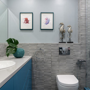 На фото: ванная комната среднего размера в современном стиле с бирюзовыми фасадами, инсталляцией, серой плиткой, керамической плиткой, полом из керамической плитки, накладной раковиной, столешницей из искусственного камня, серым полом, серой столешницей, плоскими фасадами, серыми стенами и душевой кабиной с
