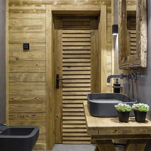 Стильный дизайн: ванная комната в стиле рустика с биде, серыми стенами, настольной раковиной, столешницей из дерева и серым полом - последний тренд